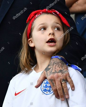 Stock Photo of Harper Beckham with David's tattooed hand next to the England badge