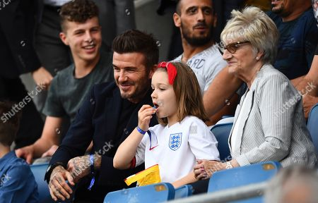 Harper Beckham eats M&M's alongside her father David