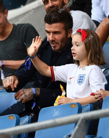 Stock Picture of Harper Beckham waves alongside her father David