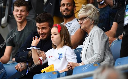 Harper Beckham waves alongside her father David