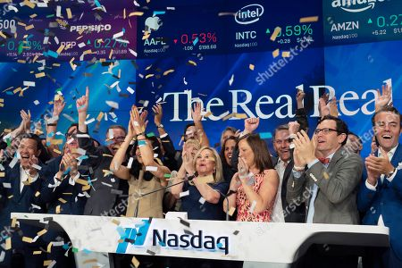Julie Wainwright, center, CEO of The RealReal, celebrates her company's IPO at the Nasdaq opening bell, in New York. The online reseller of luxury brand clothing and accessories is based in San Francisco