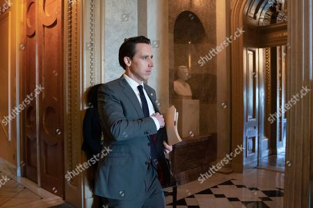 Sen. Josh Hawley, R-Mo., leaves the Senate floor after presiding over the longest roll call in history, an amendment to require approval from Congress before President Donald Trump could order military strikes against Iran, at the Capitol in Washington, . The vote will remain open all day as senators who participated in the Democratic presidential debate in Miami trickle into the chamber