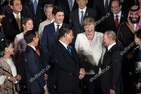 Photo family at Osaka Geihinkan during the G20 leaders summit. Wife of Joko Widodo and Indonesia's President Joko Widodo, Canada's Prime Minister Jtin Trudeau's wife Sophie Gregoire, President Xi Jinping, German Chancelor Angela Merkel and Rsia President Vladimir Putin.