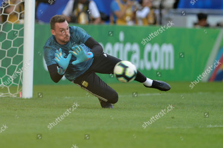 Argentina's goalkeeper Franco Armani dives for the ball while warming up prior to a Copa America quarterfinal soccer match against Venezuela at the Maracana stadium in Rio de Janeiro, Brazil