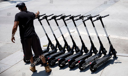 """James Wilson lines up electric scooters on a street corner after charging them overnight in Atlanta, . """"It's a good little side hustle,"""" said Wilson who has found greater fortune in charging the scooters than his old job of driving a truck. Supporters of the scooters, which have popped up in cities across the country, say they're great for short trips, but critics say they're a nuisance and can be dangerous to their drivers, pedestrians and motorists"""