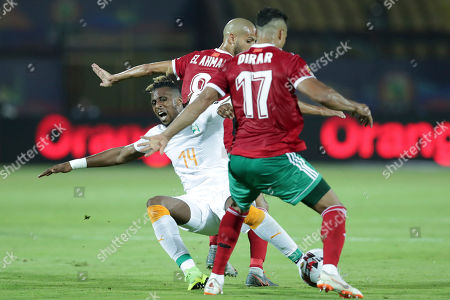 Ivory Coast's Jonathan Kodjia, center, is tackled by Morocco's Nabil Dirar, right, and Morocco's Karim El Ahmadi Aroussi during the African Cup of Nations group D soccer match between Morocco and Ivory Coast in Al Salam Stadium in Cairo, Egypt