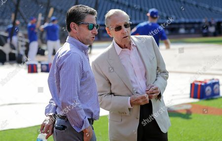 Fred Wilpon, right, majority owner of the New York Mets, and Mets COO Jeff Wilpon, left, watch the team warm up before a baseball game against the Atlanta Braves, in New York