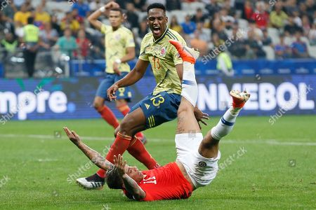 Chile's Eduardo Vargas falls after clashing with Colombia's Yerry Mina during a Copa America quarterfinal soccer match at the Arena Corinthians in Sao Paulo, Brazil