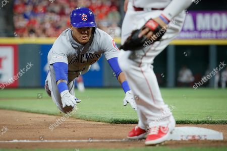 Chicago Cubs' Addison Russell slides into third with a triple off Cincinnati Reds relief pitcher David Hernandez during the seventh inning of a baseball game, in Cincinnati