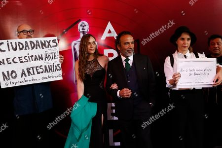 Mexican actor Damian Alcazar arrives for the 61st edition of the Ariel Awards from the Mexican Academy of Arts and Cinematographic Sciences at the National Cineteca, as demonstrators holds signs protesting against budget cuts to cultural programs, Mexico City