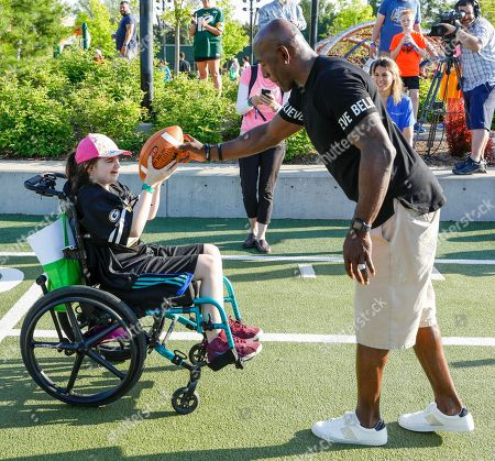 Green Bay Packers all-time leading receiver Donald Driver exchanges a pass with an attendee of Northwestern Mutual's Ultimate Campout Fighting Childhood Cancer at the Green Bay Packer's Titletown development on in Green Bay, Wis