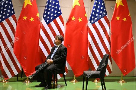 Stock Picture of A Chinese official waits on a chair in the corridors outside a bilateral meeting between Chinese President Xi Jingping and US President Donald Trump during the second day of the  summit in Osaka, Japan, 29 June 2019. It is the first time Japan will host a  summit. The summit gathers leaders from 19 countries and the European Union to discuss topics such as global economy, trade and investment, innovation and employment.