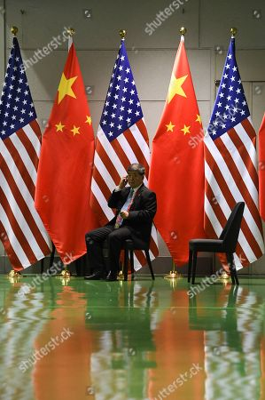 Stock Image of A Chinese official waits on a chair in the corridors outside a bilateral meeting between Chinese President Xi Jingping and US President Donald Trump during the second day of the  summit in Osaka, Japan, 29 June 2019. It is the first time Japan will host a  summit. The summit gathers leaders from 19 countries and the European Union to discuss topics such as global economy, trade and investment, innovation and employment.