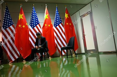 A Chinese official waits on a chair in the corridors outside a bilateral meeting between Chinese President Xi Jingping and US President Donald Trump during the second day of the  summit in Osaka, Japan, 29 June 2019. It is the first time Japan will host a  summit. The summit gathers leaders from 19 countries and the European Union to discuss topics such as global economy, trade and investment, innovation and employment.