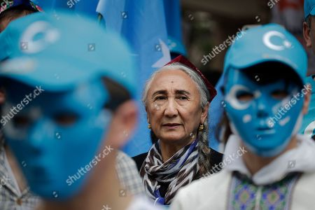 Uyghur human rights activist Rebiya Kadeer, center, stands behind protesters wearing masks in the colors of the East Turkestan flag during a rally against the Chinese government on the last day of the G-20 summit, in Osaka, Japan