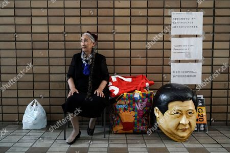 Stock Image of Uyghur human rights activist Rebiya Kadeer sits next to a mask depicting Chinese President Xi Jinping before a rally against the Chinese government on the last day of the G-20 summit, in Osaka, western Japan