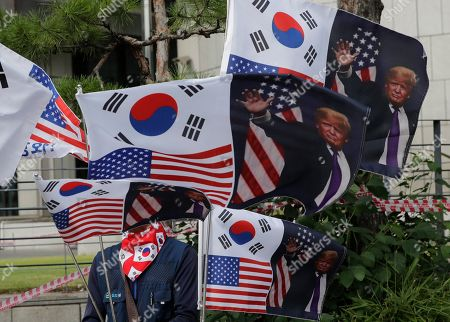 """A man holds flags with pictures of U.S. President Donald Trump in Seoul, South Korea, . North Korea said Saturday President Donald Trump's offer to meet leader Kim Jong Un at the Korean Demilitarized Zone is a """"very interesting suggestion,"""" brightening prospects for a third face-to-face meeting between the two leaders"""