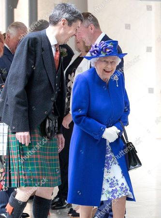 Queen Elizabeth II accompanied by Presiding Officer of the Scottish Parliament Ken Macintosh as they walk through the Garden Lobby at the Scottish Parliament in Edinburgh ahead of a ceremony marking the 20th anniversary of devolution