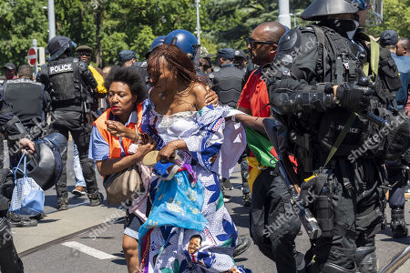 Police try to protect a woman wearing a dress adorned with pictures of Cameroon President Paul Biya being manhandled by the crowd during a protest of Cameroonian nationals living in various European countries against the presence of Cameroon President in Geneva, on the place des Nations in front of the European headquarters of the United Nations in Geneva, Switzerland, 29 June 2018.