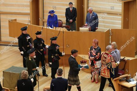 Queen Elizabeth II and the Duke of Rothesay watch as The Duke of Hamilton carries the Crown of Scotland into the Scottish Parliament in Edinburgh during a ceremony marking the 20th anniversary of devolution