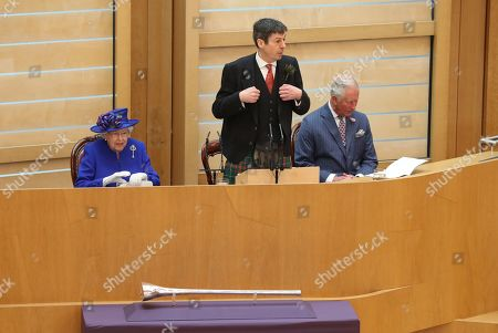 Stock Picture of Presiding Officer of the Scottish Parliament Ken Macintosh appears to perform a dance next to Queen Elizabeth II and the Duke of Rothesay, during a ceremony marking the 20th anniversary of devolution