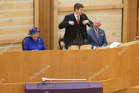 Presiding Officer of the Scottish Parliament Ken Macintosh appears to perform a dance next to Queen Elizabeth II and the Duke of Rothesay, during a ceremony marking the 20th anniversary of devolution
