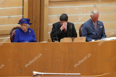 Presiding Officer of the Scottish Parliament Ken Macintosh wipes his brow as he sits alongside Queen Elizabeth II and the Duke of Rothesay during a ceremony marking the 20th anniversary of devolution
