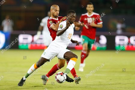 Ivory Coast's Nicolas Pepe, front, in action in front of Morocco's Karim El Ahmadi Aroussi during the African Cup of Nations group D soccer match between Morocco and Ivory Coast in Al Salam Stadium in Cairo, Egypt