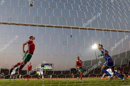 Stock Photo of Morocco's Games Saiss clears the ball from the goal line as Morocco's goalkeeper Yassine Bounou looks on during the African Cup of Nations group D soccer match between Morocco and Ivory Coast in Al Salam Stadium in Cairo, Egypt
