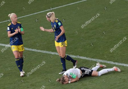 Stock Image of Caroline Seger left and Linda Sembrant of Sweden with Alexandra Popp of Germany on ground