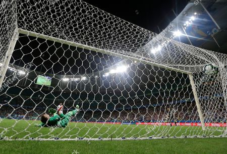 Uruguay's goalkeeper Fernando Muslera fails to stop Peru's Edison Flores from scoring the winning penalty shot in their Copa America quarterfinal soccer match at the Arena Fonte Nova in Salvador, Brazil, . Peru beat Uruguay 5-4 on penalties after the match ended 0-0