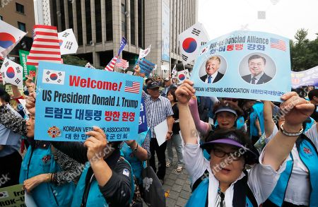"""A member of the Korean Veterans Association holds up a card showing images of U.S. President Donald Trump and South Korean President Moon Jae-in, right, during a rally to welcome his visit in Seoul, South Korea, . North Korea said Saturday Trump's offer to meet leader Kim Jong Un at the Demilitarized Zone is a """"very interesting suggestion,"""" brightening prospects for a third face-to-face meeting between the two leaders"""