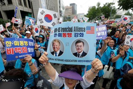 """A member of the Korean Veterans Association holds up a card showing images of U.S. President Donald Trump and South Korean President Moon Jae-in, right, during a rally to welcome a visit by Trump, in Seoul, South Korea, . North Korea said Saturday Trump's offer to meet leader Kim Jong Un at the Demilitarized Zone is a """"very interesting suggestion,"""" brightening prospects for a third face-to-face meeting between the two leaders"""