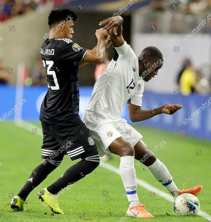 Mexico midfielder Jesus Gallardo (23) pushes Costa Rica forward Joel Campbell (12) who tries to keep the ball inbounds during the first half of a CONCACAF Gold Cup quarterfinal soccer match, in Houston