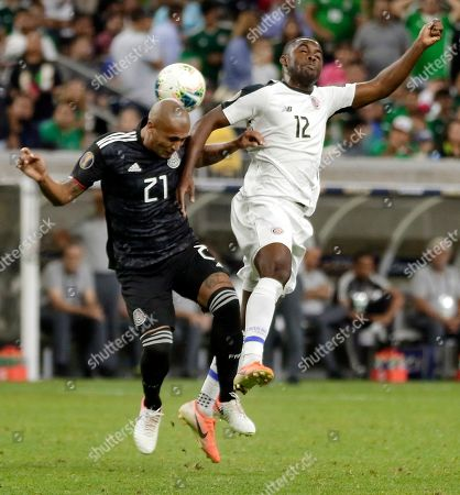 Mexico defender Luis Rodriguez (21) and Costa Rica forward Joel Campbell (12) go for a head ball during the first half of a CONCACAF Gold Cup soccer quarterfinal, in Houston