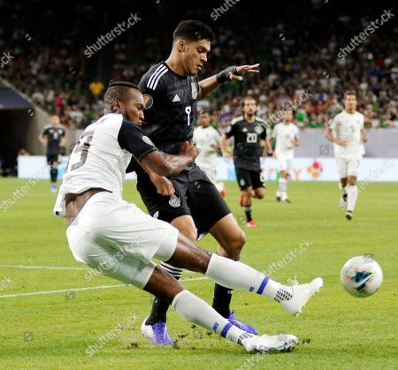 Costa Rica defender Kendall Waston (19) falls as he kicks the ball away from Mexico forward Raul Jimenez during the first half of a CONCACAF Gold Cup soccer quarterfinal, in Houston