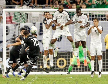 Mexico midfielder Andres Guardado (18) launches a penalty kick as Costa Rica's, from left, Bryan Ruiz, Kendall Waston (19), Mayron George (11) and Celso Borges (5) defend during the second half of a CONCACAF Gold Cup quarterfinal soccer match, in Houston