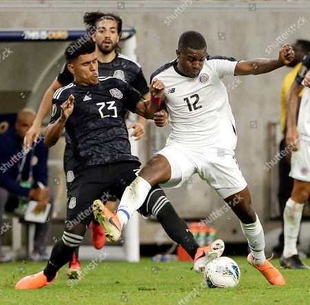 Mexico midfielder Jesus Gallardo (23) and Costa Rica forward Joel Campbell (12) battle for the ball during the second half of a CONCACAF Gold Cup quarterfinal soccer match, in Houston