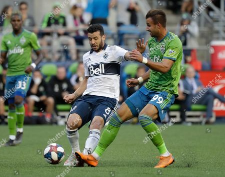 Stock Photo of Justin Dhillon, Felipe Martins. Vancouver Whitecaps' Felipe Martins (8) tries to control the ball in front of Seattle Sounders' Justin Dhillon in the first half of an MLS soccer match, in Seattle