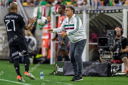 Mexico head coach Gerardo Martino tosses the ball to Mexico defender Luis Rodriguez (21) during the 1st half of a CONCACAF Gold Cup quarterfinals soccer match between Costa Rica and Mexico at NRG Stadium in Houston, TX. Mexico won on penalty kicks 1-1 (5-4)