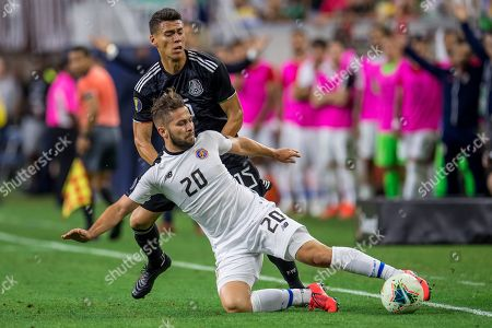 Costa Rica midfielder Elias Aguilar (20) keeps the ball in bounds in front of Mexico defender Hector Moreno (15) during the extra time period of a CONCACAF Gold Cup quarterfinals soccer match between Costa Rica and Mexico at NRG Stadium in Houston, TX. Mexico won on penalty kicks 1-1 (5-4)
