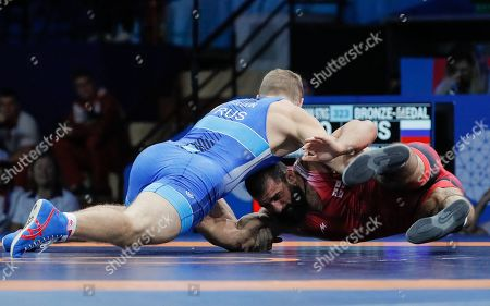 Aleksandr Golovin (blue) of Russia in action against Revazi Nadareishvili of Georgia during the Bronze medal bout of the Men's Greco-Roman -97kg category in the Sports Palace at the Minsk 2019 European Games in Minsk, Belarus, 30 June 2019.