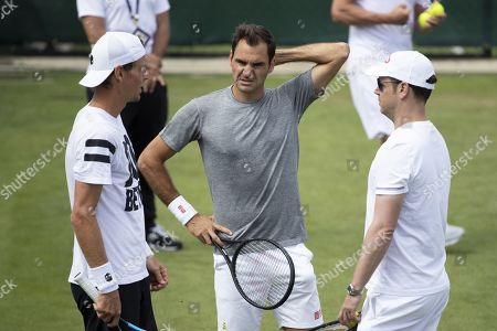 Roger Federer of Switzerland, center, talks to Tomas Berdych of Czech Republic, left, and coach Severin Luethi during a training session at the All England Lawn Tennis Championships in Wimbledon, London, on Sunday, June 30, 2019.