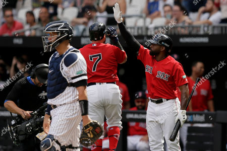 Boston Red Sox's Christian Vazquez (7) celebrates his home run with Jackie Bradley Jr., right, as New York Yankees catcher Gary Sanchez looks away during the first inning of a baseball game in London