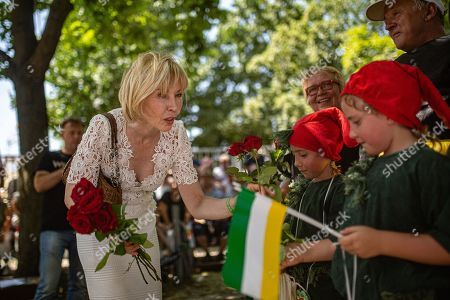 Stock Image of German journalist Doris Schroeder-Koepf (L) gives red roses to children during the marksmen's festival in Hanover, Germany, 30 June 2019. Shooting associations, members of the fire department, marching bands and other groups took part in the event that has a long tradition in Hanover.