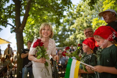 Stock Photo of German journalist Doris Schroeder-Koepf (L) gives red roses to children during the marksmen's festival in Hanover, Germany, 30 June 2019. Shooting associations, members of the fire department, marching bands and other groups took part in the event that has a long tradition in Hanover.