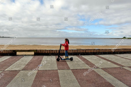 "A girl rides a scooter along the ""rambla"" during primary elections in Montevideo, Uruguay, . Uruguay's political parties are choosing their presidential candidates Sunday in a simultaneous election"