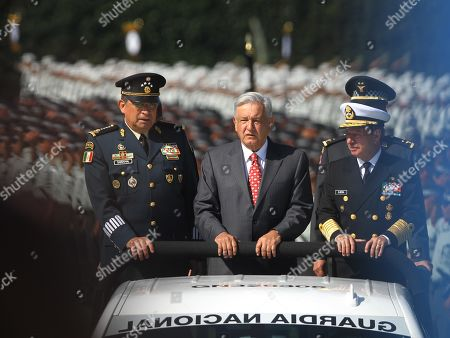 Mexican President, Andres Manuel Lopez Obrador (C), heads and reviews the National Guard, accompanied by the Secretary of National Defense, General Luis C. Sandoval (L), and the Secretary of the Navy, the Admiral Jose Rafael Ojeda (R), at the Marte militar field, in Mexico City, Mexico, 30 June 2019.