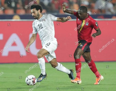 Egypt's Abdallah El Said in action in front of Uganda's Faruku Miya during the African Cup of Nations group A soccer match between Egypt and Uganda in Cairo International Stadium in Cairo, Egypt