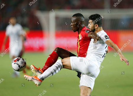 Uganda's Emmanuel Arnold Okwi, left and Egypt's Ayman Ashraf fight for the ball during the African Cup of Nations group A soccer match between Egypt and Uganda in Cairo International Stadium in Cairo, Egypt